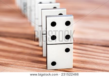Row Of Dominoes On The Wooden Table.