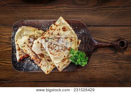 Four Sliced Wedges Of Meat And Veggie Filled Quesadillas On Black Cutting Board Over Wooden Backgrou