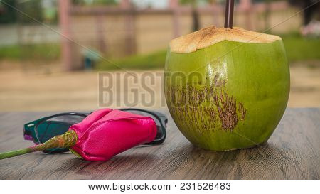 Soft Focus Of Coconut Water And Brown Tube, Sunglasses, Rose Cloth, On Wooden Table