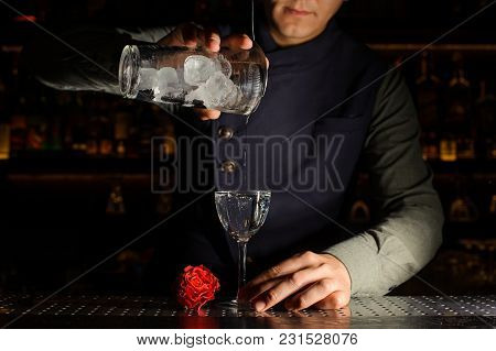 Barman Pouring A Fresh Alcoholic Drink Into A Cocktail Glass On The Bar Counter Against Dark Backgro
