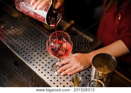 Female Barman Hands Pouring Fresh And Sweet Red Alcoholic Drink Into A Cocktail Glass With Ice Cube