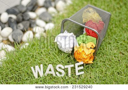Blurred Image Concept Alphabet Word Waste Made From Wood On Grass. Ball Paper And Metal Dustbin