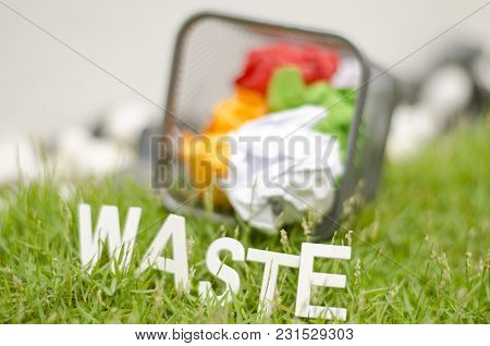Blurred Image Of Word Waste Made From Wood In Arc Position Placed On Green Grass. Ball Used Colour P
