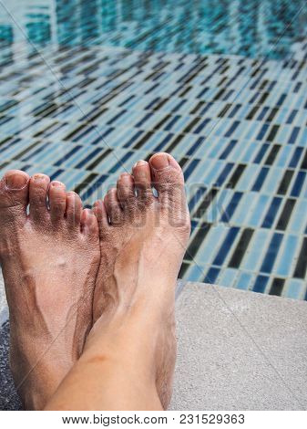 Feet On The Cement Floor Beside The Pool.