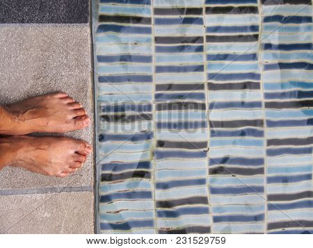 Feet On The Cement Floor Beside The Pool