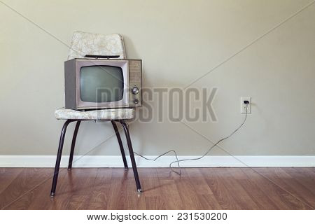Vintage Television on an old chair against a blank wall