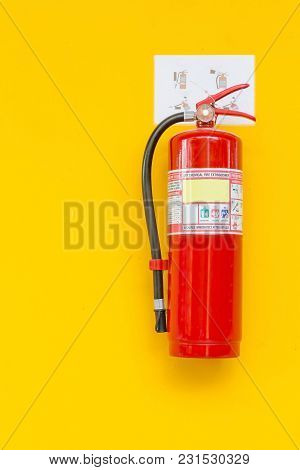 Fire Extinguisher On The Yellow Wall. Safety
