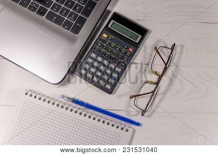 White Office Desk With Laptop, Calculator, Notepad, Eyeglasses And Pen. Top View