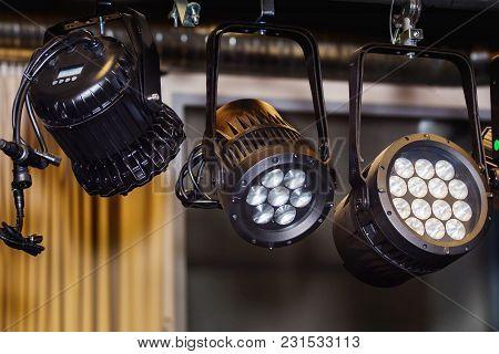 Three black spotlights on a stage. Close up.