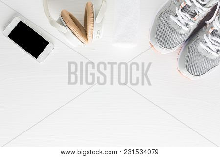 Flat Lay Of Fitness Accessories On White Wooden Background. Running Shoes, Towel, Smartphone And Hea