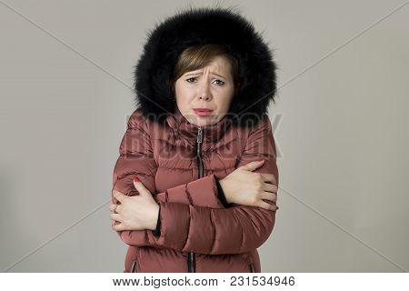 young read hair attractive and sweet woman 20s or 30s posing isolated wearing warm winter jacket with fur hood shivering and freezing feeling cold in sweet face expression poster