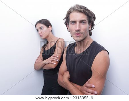 sad couple standing near a white wall.