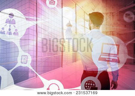 Businessman pretending to touch invisible device screen against modern room overlooking city