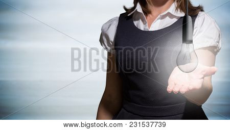 Digital composite of Business woman mid section with glowing light bulb against blurry blue wood panel