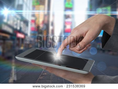 Digital composite of Hands touching tablet against blurry street with flares and bokeh