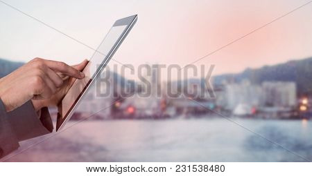 Digital composite of Hands with tablet against blurry skyline and red overlay