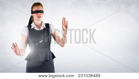 Digital composite of Business woman blindfolded against white wall and flare