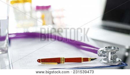 Closeup Of The Desk Of A Doctors Office With A Stethoscope In The Foreground And A Bottle With Pills