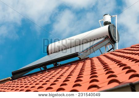 Solar Water Heater On Roof Top, Beautiful Blue Sky Background.