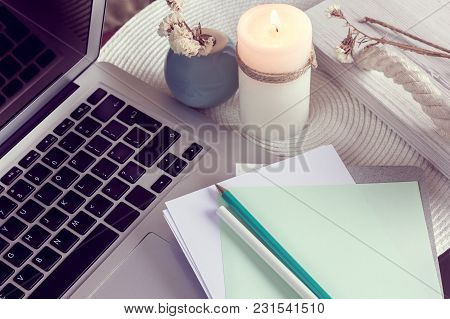 The Notebook With Pencils On A Table And Laptop With Candle And Vase