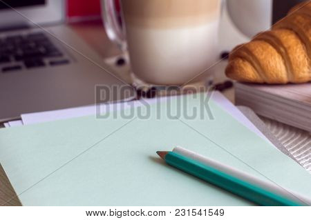 The Notebook With Pencils On A Table And Laptop With Coffee And Croissant