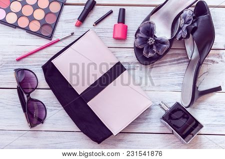 Pink Handbag And Black Stiletto Heels With Perfume And Cosmetics On A White Wooden Background