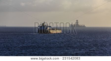 Empty Tanker Sailing Past Oil Rig On Horizon