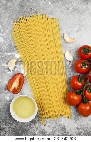 Raw Pasta And Ingredients For Cooking (cherry Tomatoes, Olive Oil, Garlic) On Gray Background. Top V