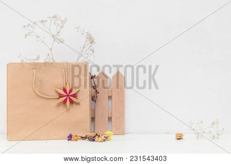 Composition Of Paper Bag, Dried Flowers And Decoration On White Cracked Wall Background.