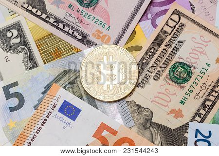 Golden Cruptocurrency Bitcoin On Dollar And Euro Background. High Resolution Photo.