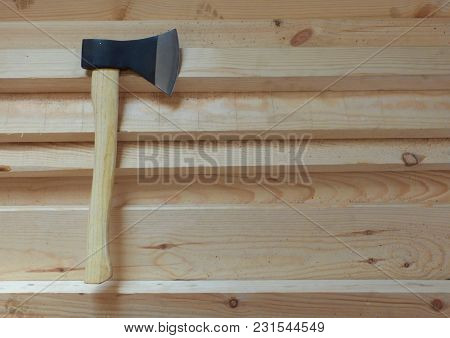 Big Sharp Ax With Black Blade And Light Yellow Handle On Fresh Wooden Boards. Wood Chopping, Constru