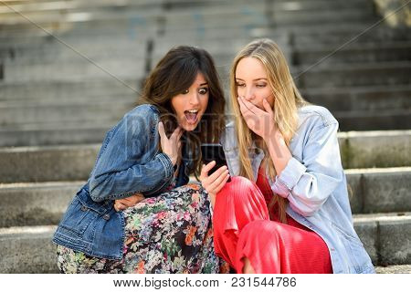 Two Women Amazed By What They See On Their Smart Phone