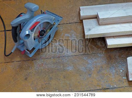 New Fresh Boards And Electric Circular Saw On Aged Wooden Surface (floor Or Table). Abstract Constru