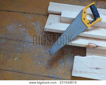 New Fresh Boards And Saw On Aged Wooden Surface (floor Or Table). Abstract Construction Background.