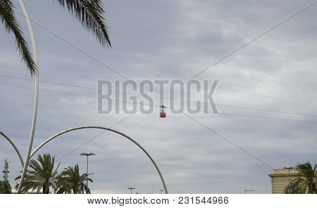 Red Cabin On Cableway. Red Cable Car In The Sky Of Barcelona, Spain