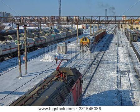 Snow Removal Train Clears Railway At The Station. Lot Of Cargo Cars And Oil Tanks At The Back. Locom