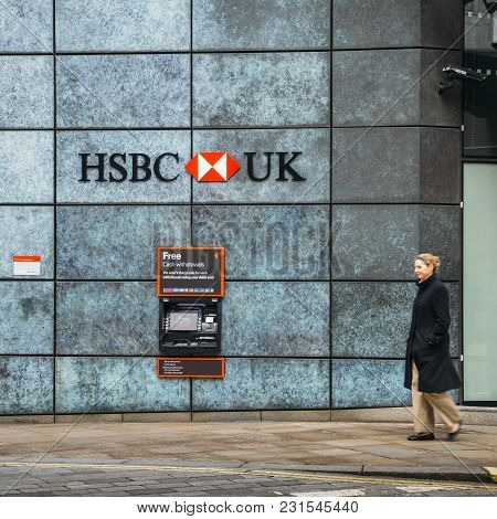 London, Uk- Mar 13, 2018: Middle Aged Woman Walks Past An Automatic Teller Machine From The Hsbc Ban