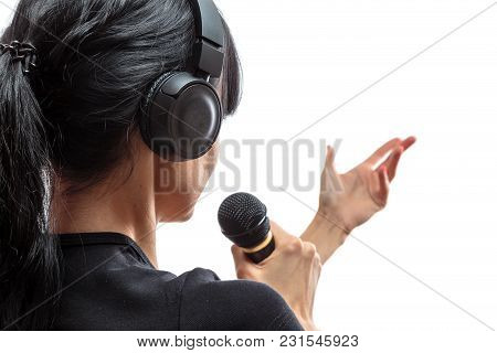 Wireless Headphones Are On The Head Of A Young Girl Brunettes With Long Hair With Microphone In Hand