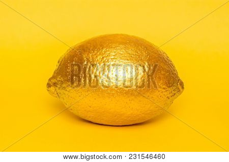 Gold Lemon On Yellow Background. Creative Concept With Fruit