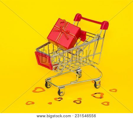 Shopping Trolley With Red Gift And Red Confetti On A Yellow Background