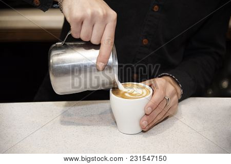 In A White Cup With A Coffee Drink, The Barman Adds Milk.