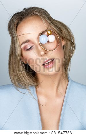 Beautiful Young Woman With Natural Makeup And Long Hair. Pastelle Jewerly On Eye. Beauty Studio Shot