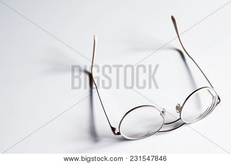Light Metal Rim Teen Glasses Isolated On White Table Surface With Copy Space For Text.