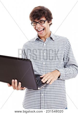 Young hispanic man wearing blue checkered shirt and black glasses reading something funny from his laptop and loudly laughing isolated on white background - internet humor and fun