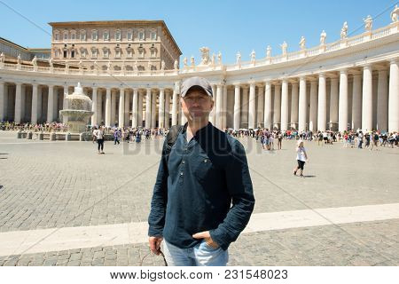 Man posing over St. Peter's Cathedral, Vatican, wide angle view. Handsome middle-aged man in St. Peter's Square. 10 of July 2017.