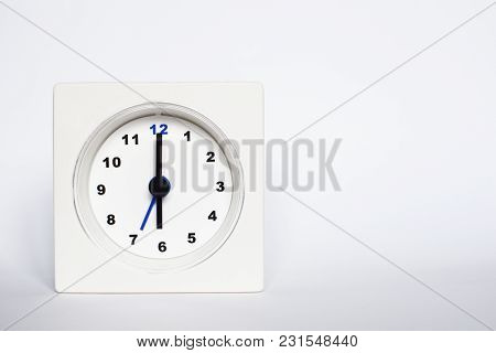 White Square Shape Alarm Clock On White Background. Concept Of Early Morning Wake Up Time.