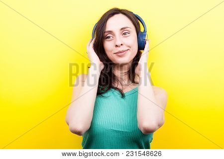 Funny Girl Listening To Music In Her Headphones On Yellow Background In Studio