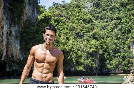 Half Body Shot Of A Handsome Young Man Standing On A Beach In Phuket Island, Thailand, Shirtless Wea