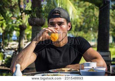 Attractive Young Man Eating Breakfast Outdoor, Having A Slice Of Bread With Jam And Butter And Drink
