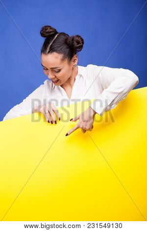 Happy Woman Holding A Yellow Banner In Hands Over Blue Background In Studio Photo